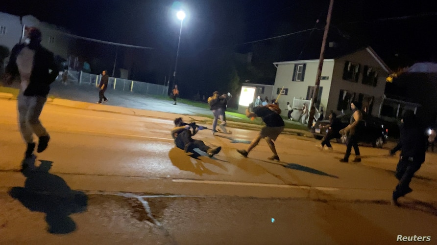 Men scuffle during a protest following the police shooting of Jacob Blake, a Black man, in Kenosha, Wisconsin, U.S., August 25,…