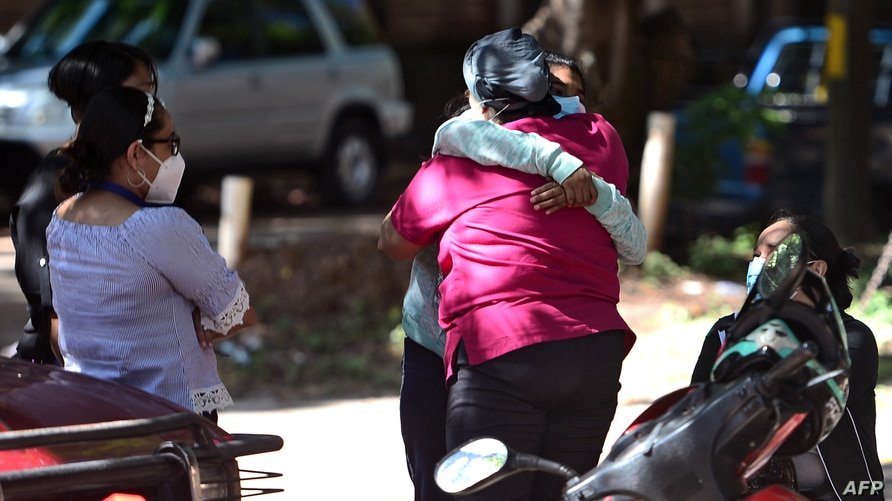 Relatives and friends embrace as they wait for the remains of murdered Honduran journalist Luis Almendares, outside the…