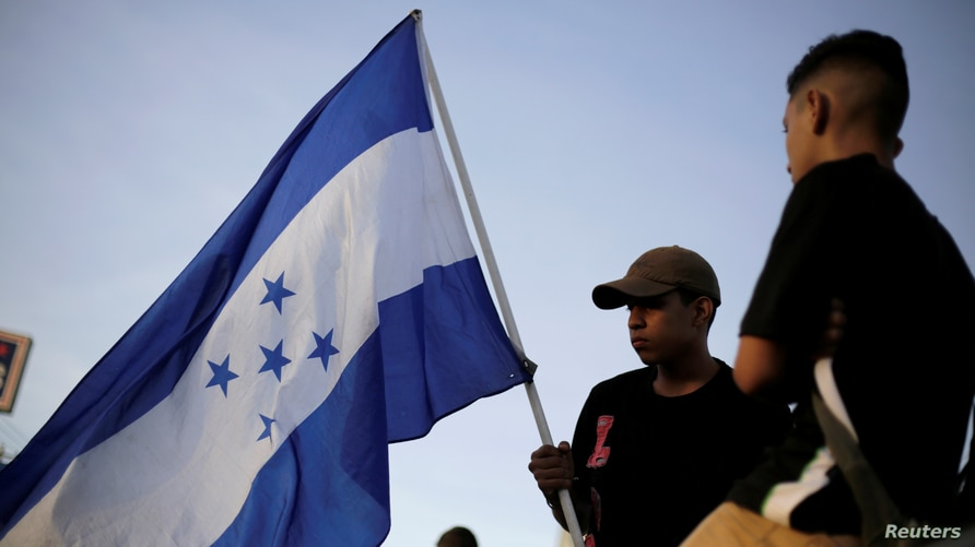 A demonstrator holds a Honduran flag during a protest to mark the first anniversary of a contested presidential election with…