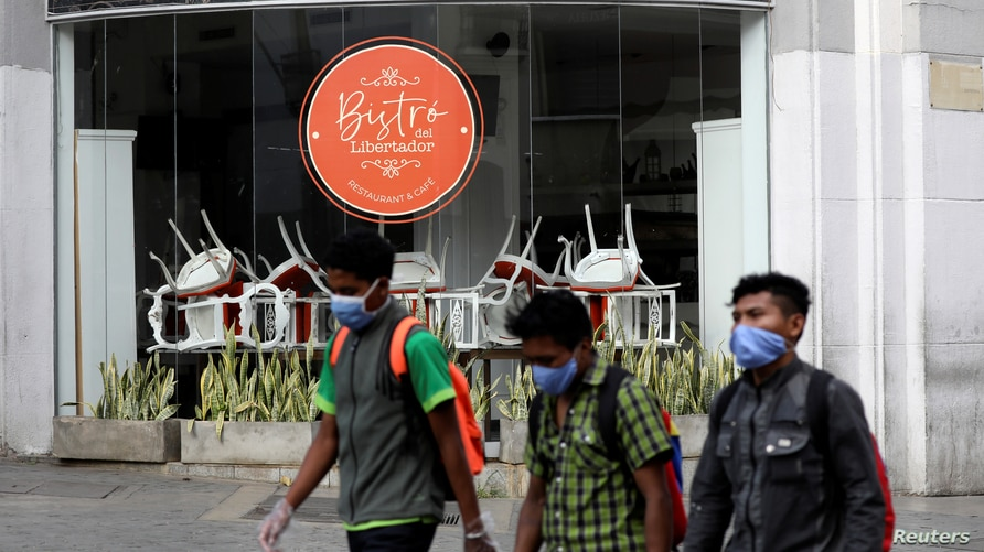 People wearing protective mask walk past a closed restaurant during a national quarantine in response to the spread of…