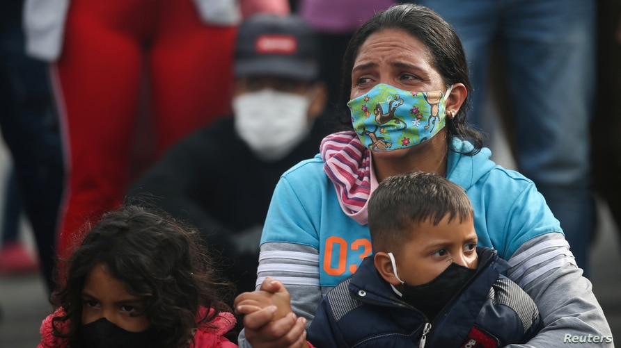 A Venezuelan migrant woman wearing a face mask holds a child as she participates in a protest against the blockade of buses…