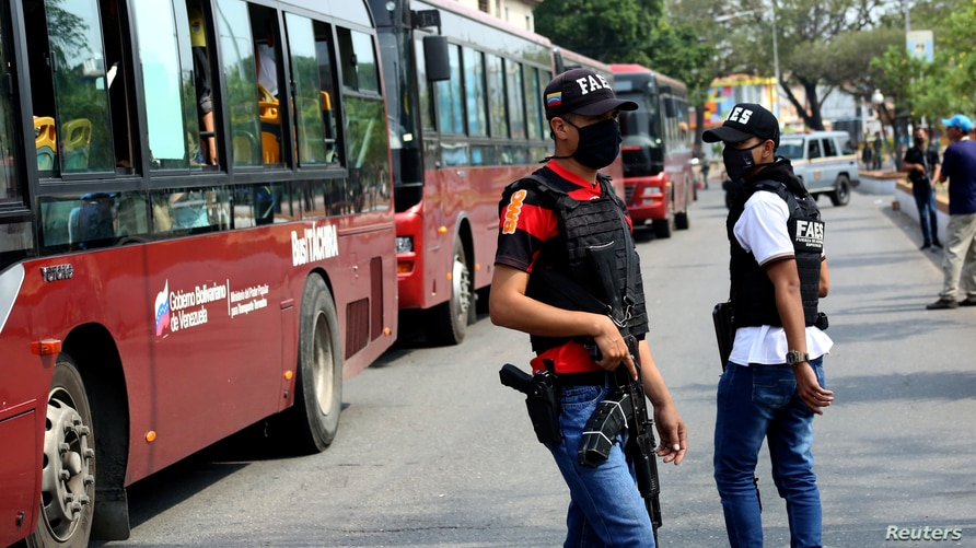 Members of the special forces unit (FAES) stand next to buses with Venezuelan citizens returning to their country after…