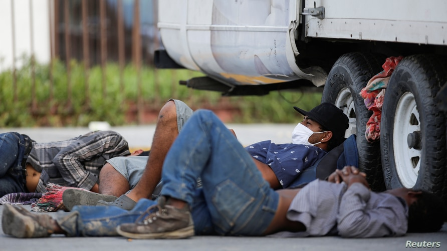 "Migrants rest beside a truck outside the migrant shelter ""Casa INDI"", where some migrants have been infected by the coronavirus…"