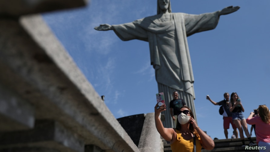Tourists take photos at the Christ the Redeemer statue during the reopening after months-long closure due to the outbreak of…