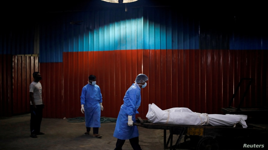 A health worker wearing personal protective equipment (PPE) carries the body of a man, who died due to the coronavirus disease …