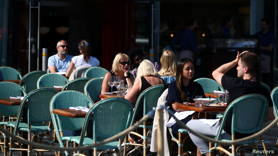 People eat in an outdoor restaurant during lunchtime, as the spread of coronavirus disease (COVID-19) continues, in London,…