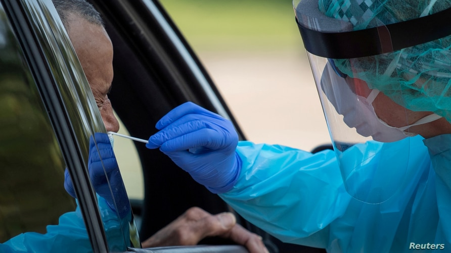 FILE PHOTO: A healthcare worker uses a swab to test a man at a coronavirus disease (COVID-19) drive-in testing location in…