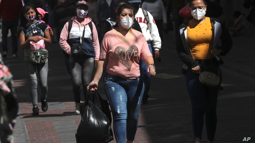 People wearing masks to curb the spread of the new coronavirus walk in downtown Quito, Ecuador, Monday, Sept. 14, 2020. Ecuador…