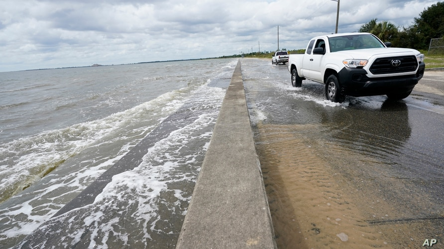 Waters from the Guld of Mexico poor onto a local road, Monday, Sept. 14, 2020, in Waveland, Miss. Hurricane Sally, one of a…