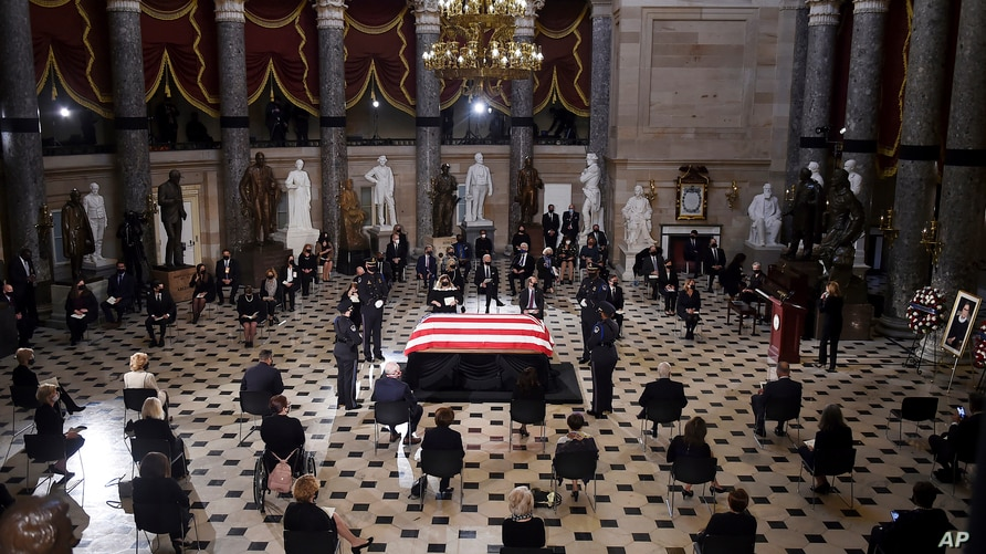 Members of Congress and guests pay their respects as the flag-draped casket of Justice Ruth Bader Ginsburg lies in state at the…