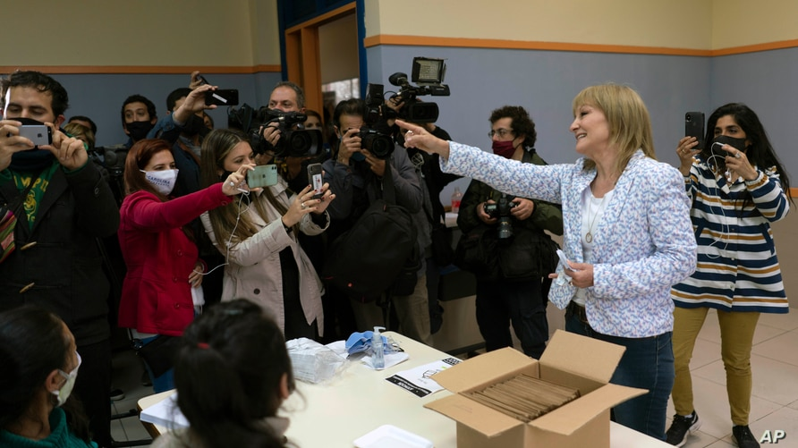Carolina Cosse, mayoral candidate from the Frente Amplio party, smiles to journalists before casting her vote at a polling…