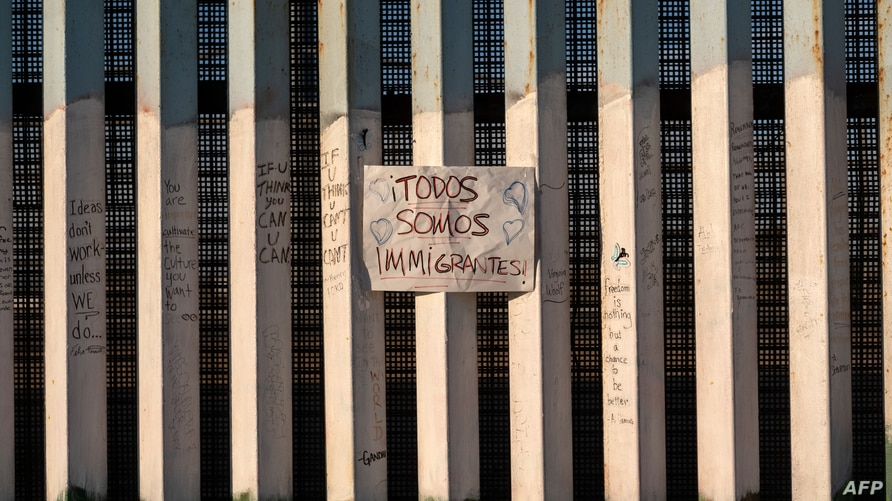 "A sign on the US-Mexico border reads in Spanish ""Todos somos migrantes"", (we are all immigrants) in Playas de Tijuana,…"