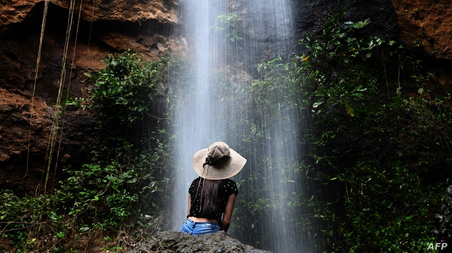 A tourist sits below a waterfall during the gradual reopening of tourism in El Salvador after the mandatory quarantine to…