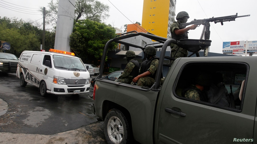 Soldiers escort a forensic vehicle carrying the body of Pedro Velazquez, a former policeman linked to the Beltran Leyva Cartel,…