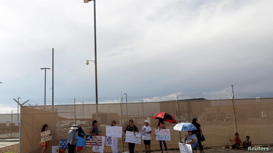 Activists hold placards as they protest against the detention of immigrant children in detention centers, outside a U.S…