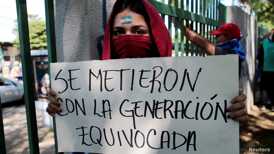 """A masked university student holds a banner that reads """"They messed with the wrong generation"""" during a protest against…"""
