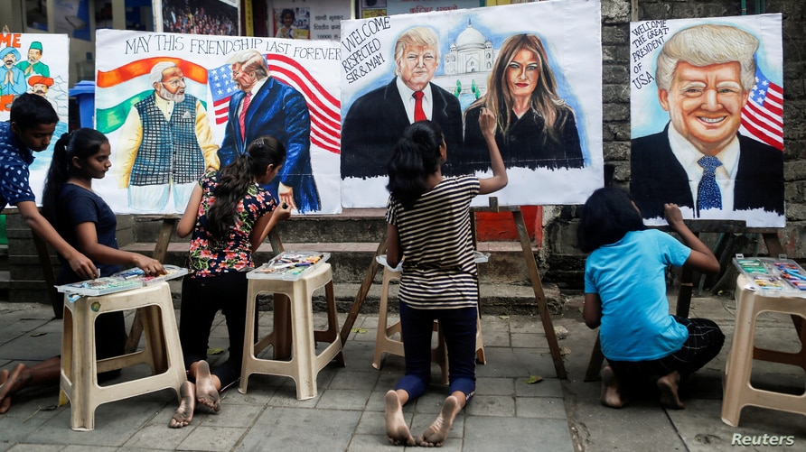 Students paint murals of U.S. President Donald Trump and first lady Melania Trump on canvas sheets along a street in Mumbai,…