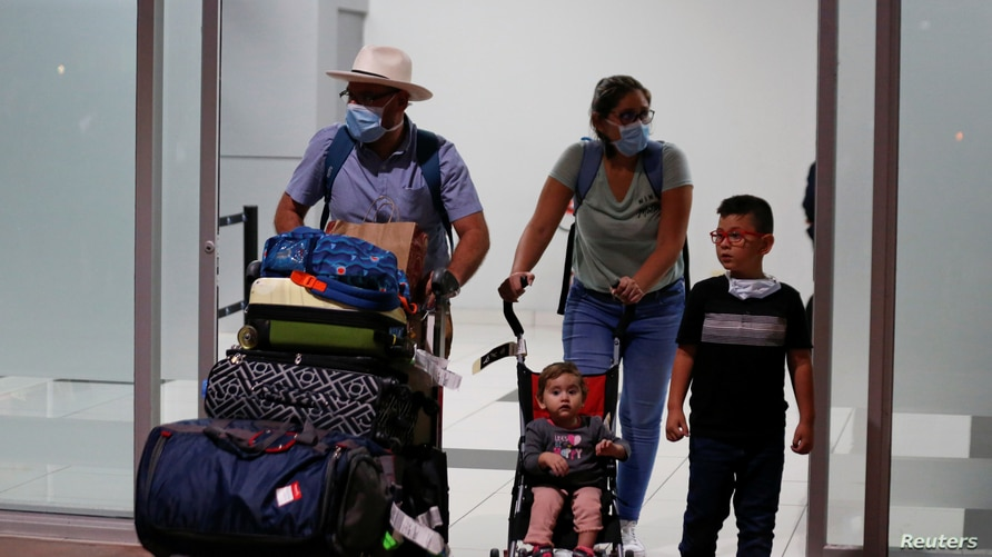 Travellers wear protective face masks as they arrive at the El Salvador International Airport Saint Oscar Romero y Galdamez…