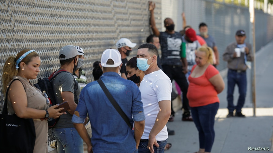 """Migrants in the """"Remain in Mexico"""" program queue outside the premises of the National Migration Institute (INM) to renew their…"""