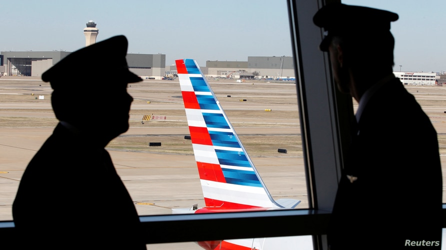FILE PHOTO: Pilots talk as they look at the tail of an American Airlines aircraft at Dallas-Ft Worth International Airport…