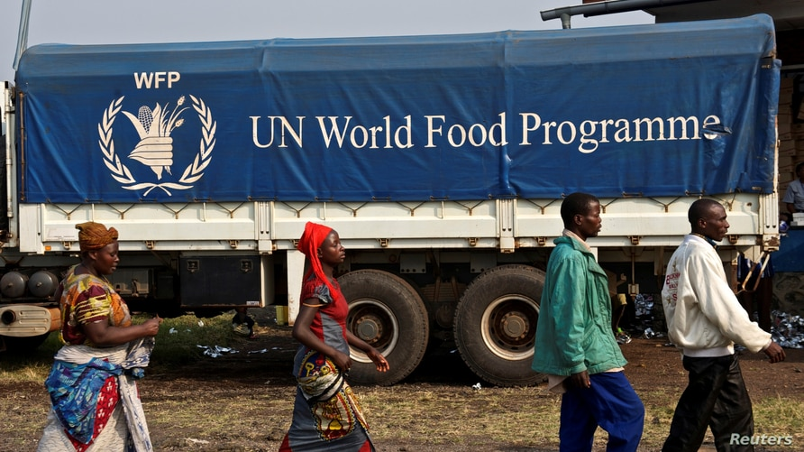 FILE PHOTO: Displaced Congolese civilians walk past a truck carrying food for distribution at Kibati, just outside the eastern…