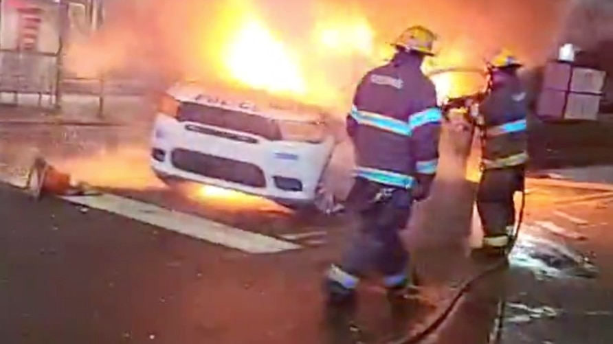 Firefighters hose down a burning police vehicle during protests after the death of Walter Wallace Jr., a Black man who was shot…