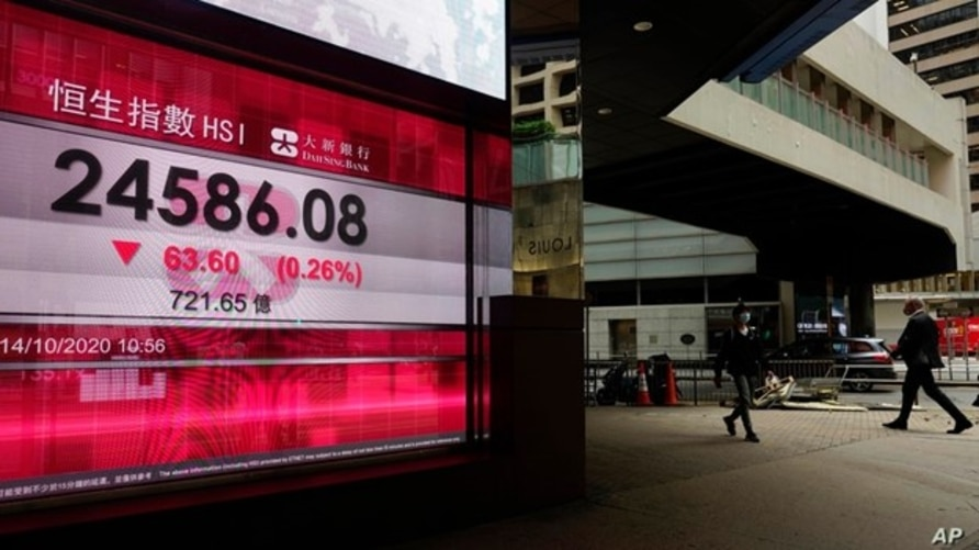 People walk past a bank's electronic board showing the Hong Kong share index at Hong Kong Stock Exchange, Oct. 14, 2020.