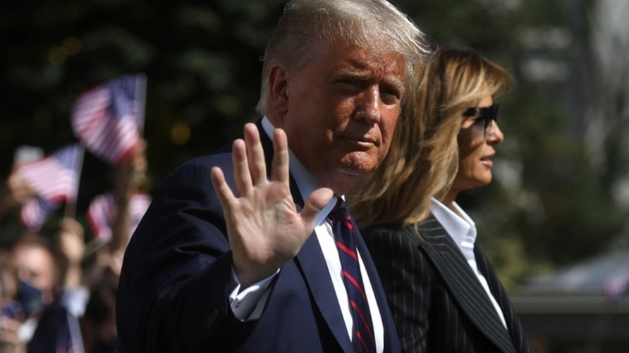 FILE - U.S. President Donald Trump waves to reporters as he departs with first lady Melania Trump to participate in his first presidential debate with Democratic presidential nominee Joe Biden in Cleveland, Ohio, Sept. 29, 2020.