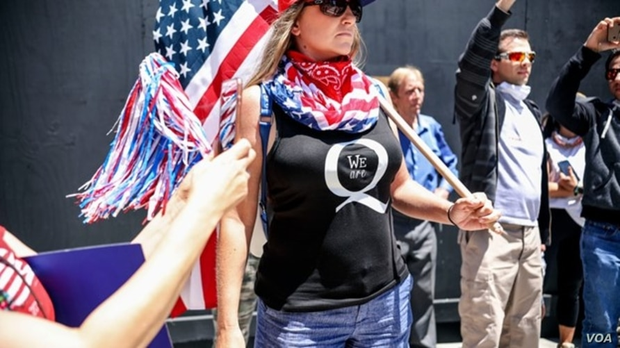 FILE- May 01, 2020, conspiracy theorist QAnon demonstrators protest during a rally to re-open California against Stay-At-Home directives. YouTube said October 15, 2020 it was tightening propagation of conspiracy theories, targeting the QAnon movement.