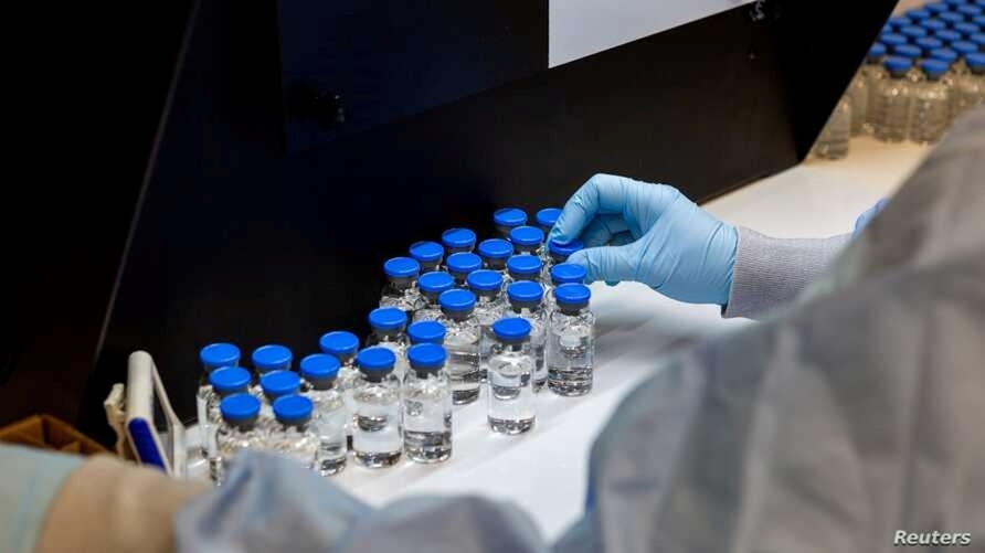 FILE - A lab technician inspects vials with the investigational coronavirus disease treatment drug remdesivir at a Gilead Sciences facility in La Verne, California, March 11, 2020.
