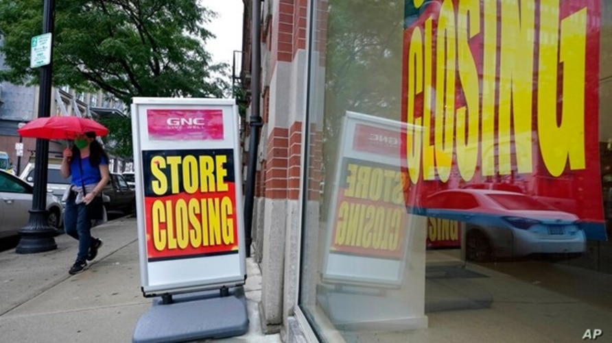 FILE - A passer-by is shown near a storefront with closing signs in Boston, Sept. 2, 2020. The U.S. unemployment rate dropped to 7.9% in September, but hiring is slowing and many Americans have given up looking for work, federal officials say.