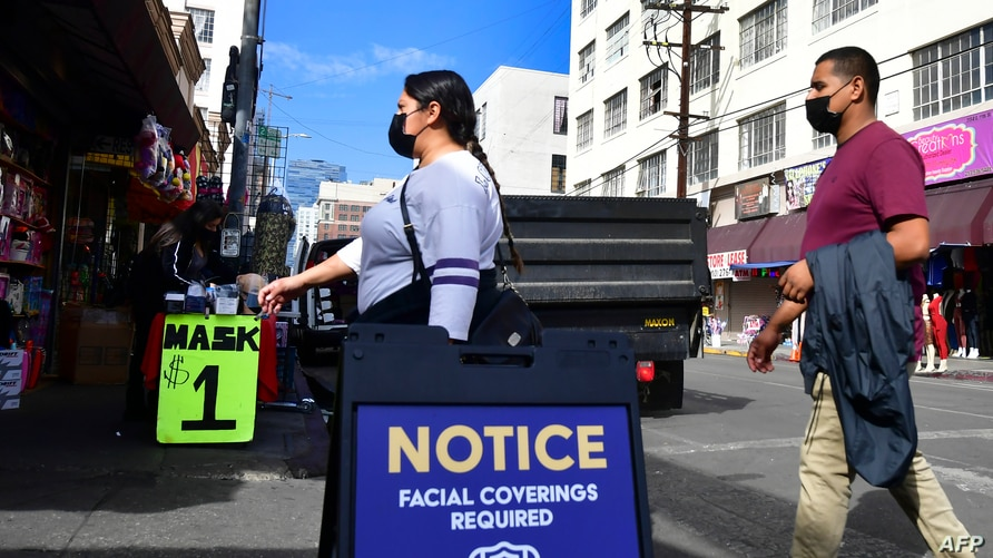 A signboard reminds people of the face covering requirement as pedestrians wear facemasks due to the coronavirus in Los Angeles…