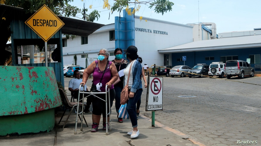 A patient walks with a relative after a consultation at the Aleman-Nicaraguense hospital, amid the outbreak of the coronavirus…