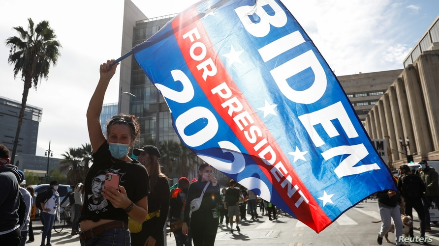 A person waves a flag after media announced that Democratic U.S. presidential nominee Joe Biden has won the 2020 U.S…