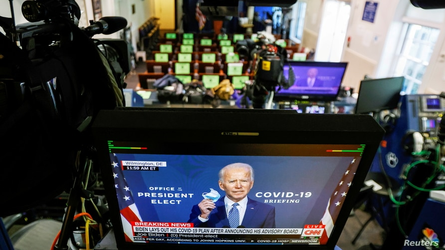 U.S. President-elect Joe Biden is seen making remarks on his plan to fight COVID-19 on television monitors from the White House…