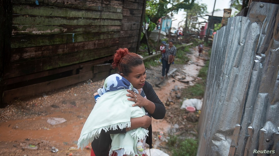 A woman protects her baby from the rain as Hurricane Iota approaches Puerto Cabezas, Nicaragua November 16, 2020. REUTERS…