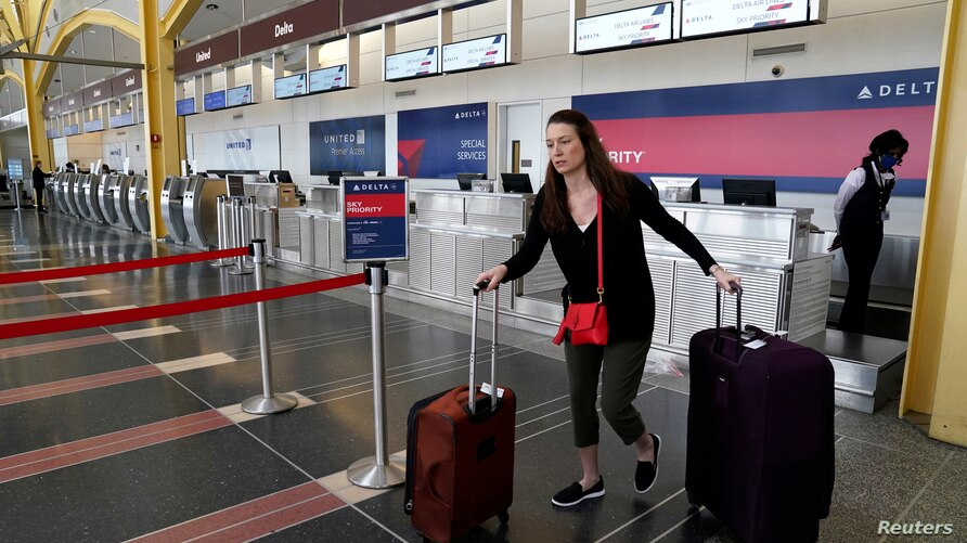 FILE PHOTO: A passenger leaves a Delta Airlines counter after checking in for a flight at Reagan National airport in Washington…