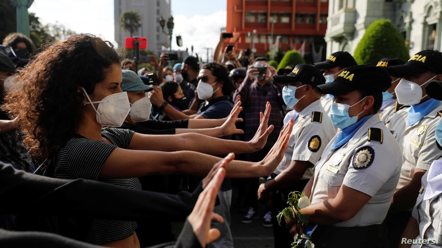 Demonstrators gesture in front of police officers during a protest to demand the resignation of Guatemala's President Alejandro…