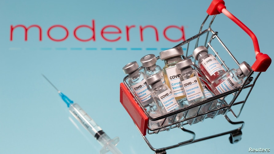 """A small shopping basket filled with vials labeled """"COVID-19 - Coronavirus Vaccine"""" and a medical sryinge are placed on a…"""
