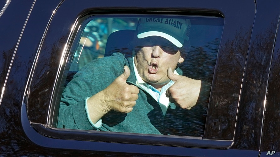 President Donald Trump gives two thumbs up to supporters as he departs after playing golf at the Trump National Golf Club in…