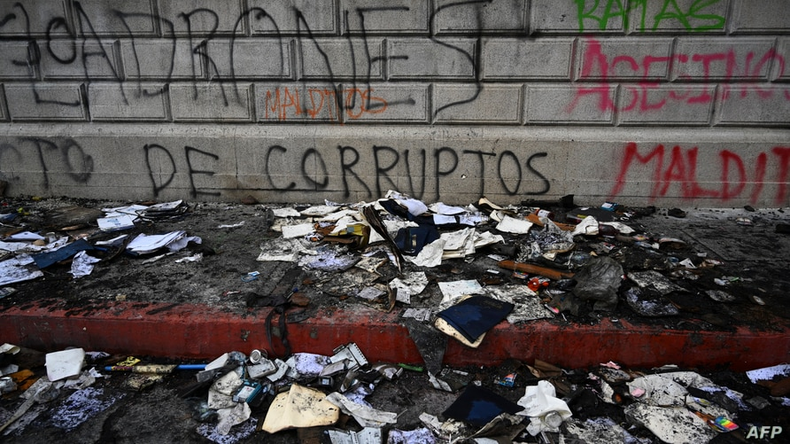 Damaged documents are seen outside the Congress a day after it was patrly burned during a protest demanding the resignation of…