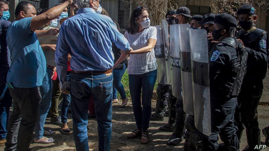 Nicaraguan journalist Carlos Fernando Chamorro (2-R), director of Confidencial and Esta Semana news media, is pushed away by…