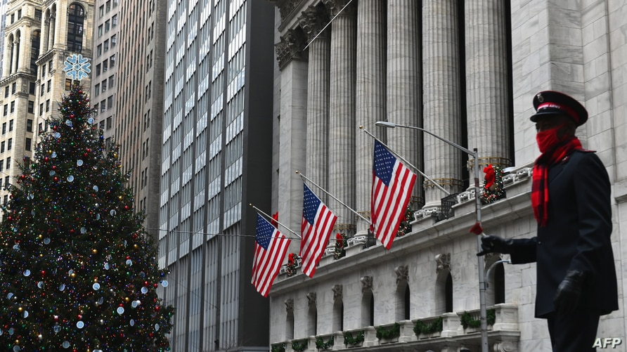 (FILES) In this file photo taken on December 09, 2020, a Salvation Army volunteer dances in front of the New York Stock…