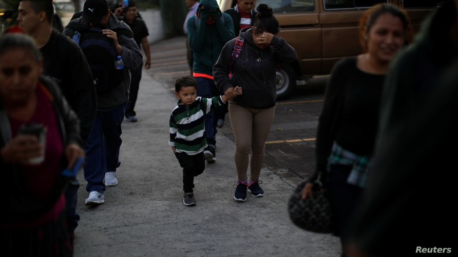 A mother and son walk in a caravan of migrants departing from El Salvador en route to the United States, in San Salvador March…