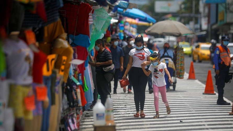 People walk along a commercial area in downtown San Salvador, after El Salvador's President Nayib Bukele postponed the second…