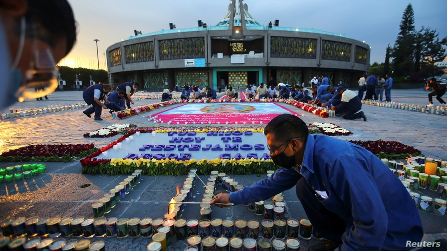 A man lights candles on behalf of the faithful at Basilica of Guadalupe that is temporarily closed to avoid crowds on the…