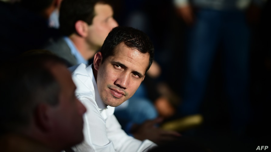 Venezuelan opposition leader and self-proclaimed interim president Juan Guaido attends a meeting with local leaders in Caracas,…