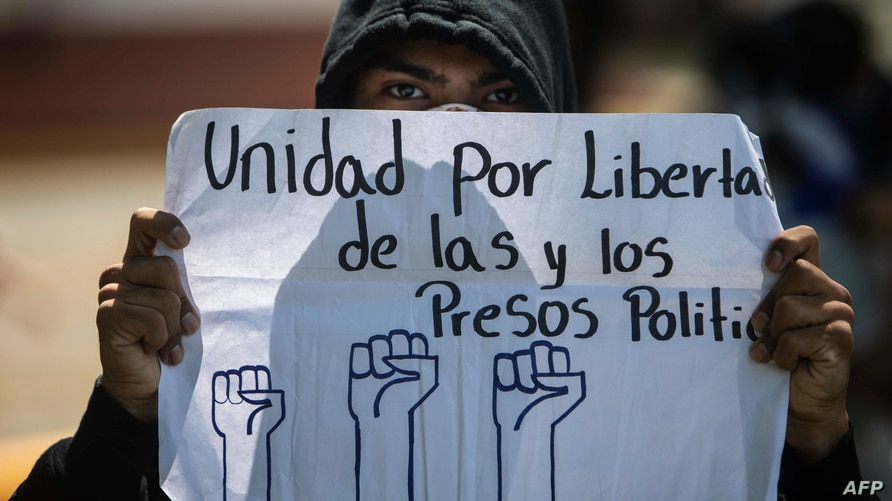 A university student holds a sign reading 'Unity for political prisoners freedom' during a protest demanding Nicaraguan…