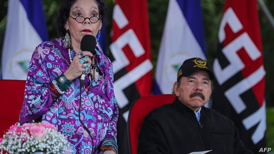 Handout picture released by the Nicaraguan Presidency showing Nicaraguan President Daniel Ortega (R) listening to his wife and…