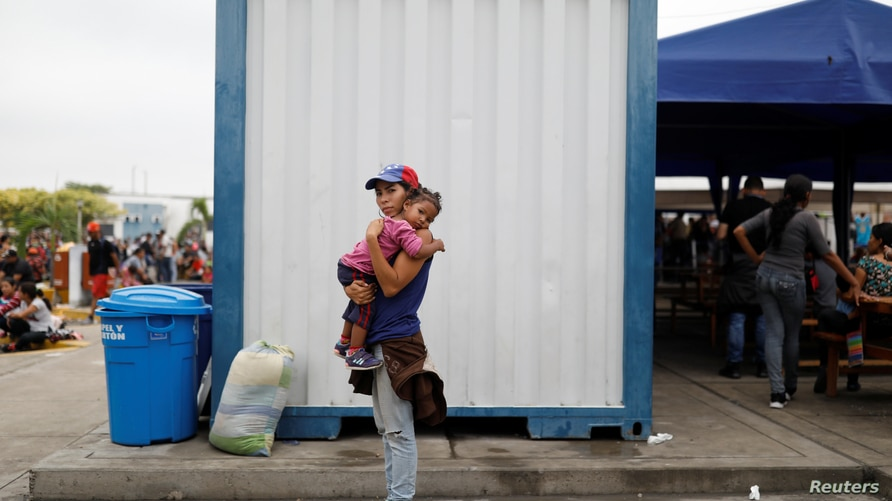 Venezuelan migrant Andraimi Laya, 22, poses for a picture carrying her daughter Jessy, while they wait to process their…